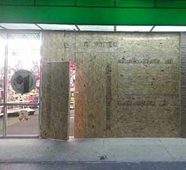 a shop with windows boarded up