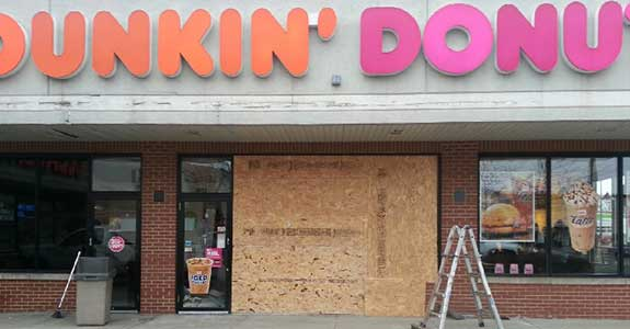 A donut shop with a boarded up broken window