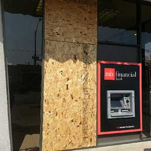 A boarded up window next to an ATM machine